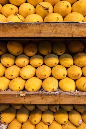 Pile of fresh yellow ripped Thai mango names Mamuang Kaew displayed on fruits stall shop