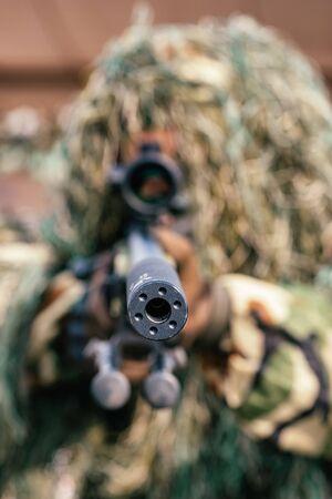 Camouflaged sniper keeps victim at gunpoint Фото со стока