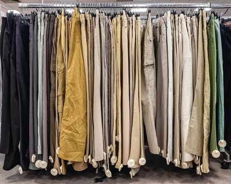 The Secondhand clothes in the market. Pants in used clothes shop Фото со стока