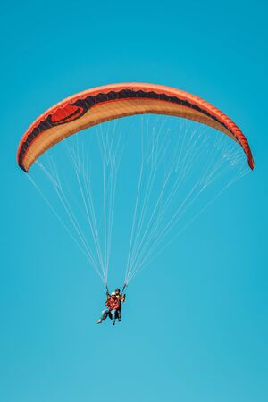 Colorful paraglider on blue bright sky close-up Фото со стока