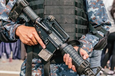 Unrecognised military soldier holding his assault rifle close-up Фото со стока