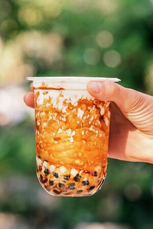 Woman hand holding iced milk bubble tea with tapioca pearls and caramel Stock Photo
