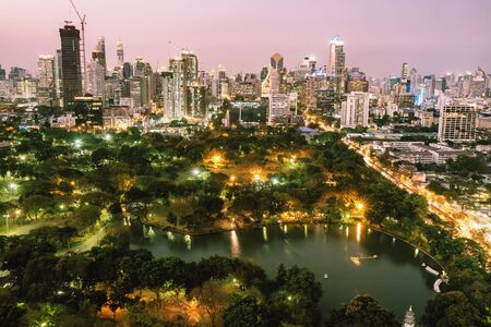 Bangkok city skyline with Lumpini park and urban skyscrapers at twilight