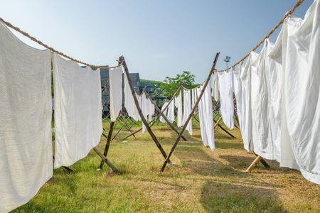 Laundry drying on a rope in the yard in the sunlight. White bed sheets and towels drying in indian traditional laundry Dhobi Ghat in Fort Kochi Stock Photo