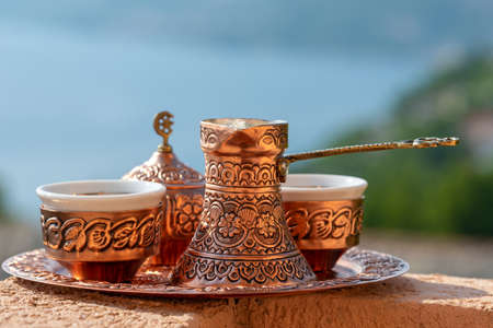 Traditional black bosnian coffee in beautiful copper cezve at wooden table