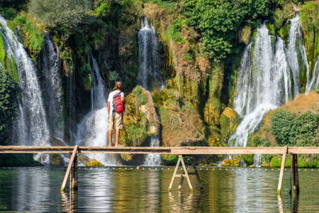 Unidentified tourist stands on the wooden bridge in front of beautiful Kravica waterfall in Bosnia and Herzegovina