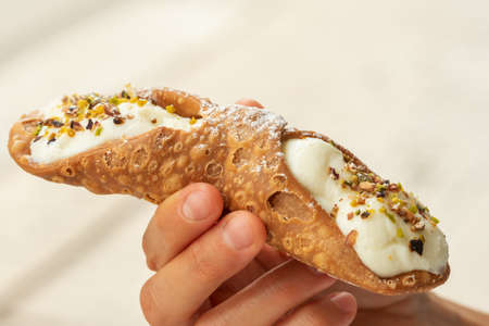 Close up of a fresh Sicilian Cannoli, held by hand. .