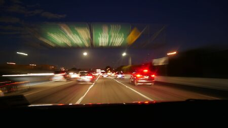 Los Angeles freeway traffic in motion at night heading down town 写真素材