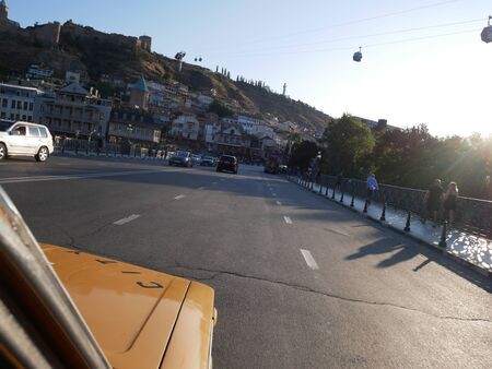 Having a ride in old yellow lada in Tibilisi in sunny summer day