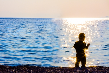 Child on beach looking the sea photo