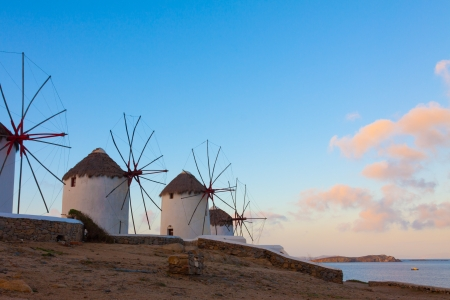 Windmills at dawn with partialy blue sky a clouds Mykonos island cyclades Greece photo