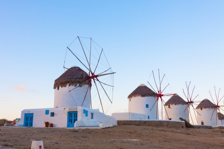 Windmills in a row from distance at dawn with partialy blue sky Mykonos island cyclades Greece