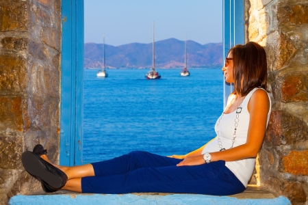 Young woman relaxing looking at sailing boats threw window frame photo