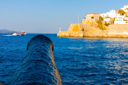 Rusty aged canon aiming at flying dolphin in Hydra Island Saronikos gulf in greece Stock Photo - 17406496