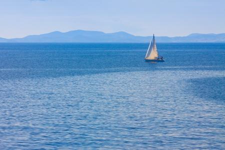 Sailing boat by Mykonos island in cyclades Greece sailing away photo