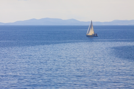 Sailing boat by Mykonos island in cyclades Greece sailing away