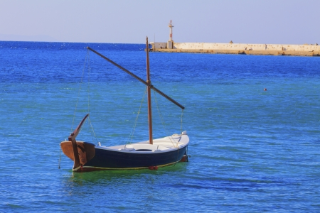 Single wooden fishing boat in Mykonos Old Port Greece Cyclades