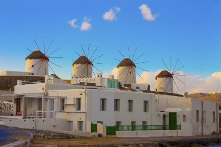 zoomed in: Windmills from distance zoomed in with clouds on sky in Mykonos Island cyclades Greece Stock Photo