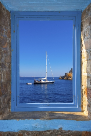 View of a sailing boat threw a window  in Santorini island Greece photo