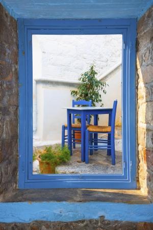 skiathos: View of a traditional ouzeri table threw a window in  in Santorini island Greece