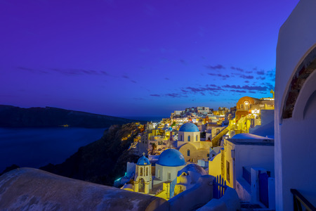 Dusk overlooking buildings on the Caldera at Oia Santorini Greece Europe at night with sea background Stock Photo