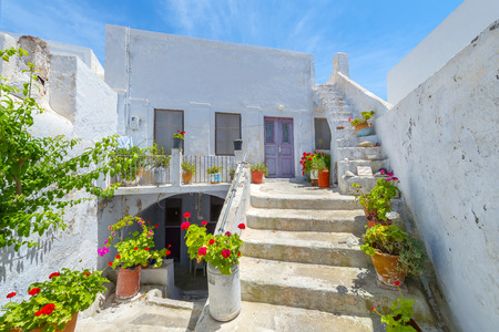 Greece Santorini island in cyclades colorful view of whitewashed houses among small walk paths that cross the island with wooden door frames and flower pots