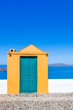 Greece Santorini island in Cyclades, door to nowhere with wooden frame and caldera sea in background Stock Photo