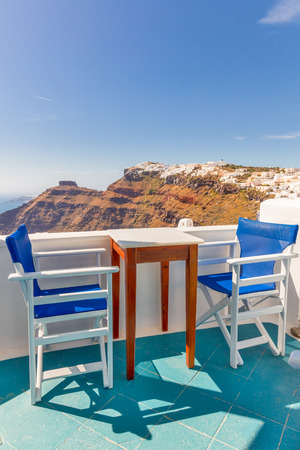 Greece Santorini island in Cyclades, greek caffe shop with Oia over caldera in background Stock Photo