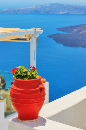 Greece Santorini island in Cyclades, traditional detail sights of colorful flowers with pots and caldera sea in background photo