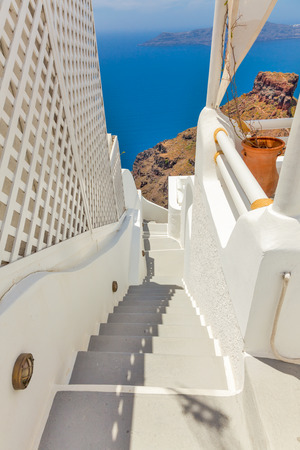 Greece Santorini island in Cyclades, traditional sights of colorful and white washed walk paths like narrow streets and caldera sea in background Stock Photo