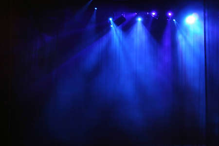 light show: Blue stage light behind curtain Stock Photo