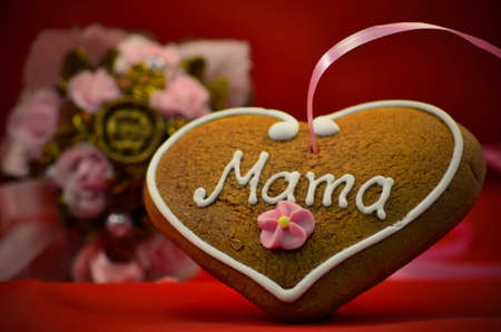 Mothers day gingerbread heart with bouqet in background photo