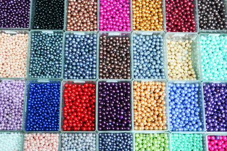 Multicolored assorted beads set in a box. Hand made jewelry. Abstract background. Stock Photo