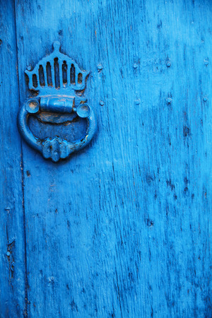 Old wooden light blue door with aged metal door handle
