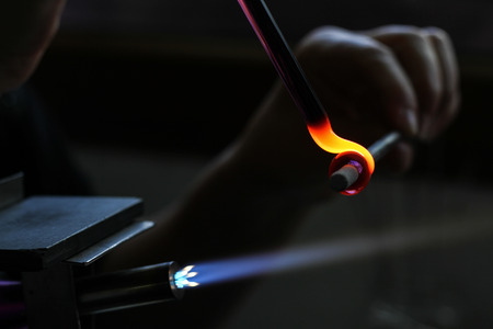 womans hands with tools for glass melting