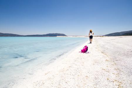 Woman tourist walking on tropical summer vacation wearing sun hat