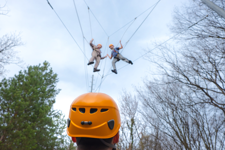 men at adventure climbing park walks by a rope simulator