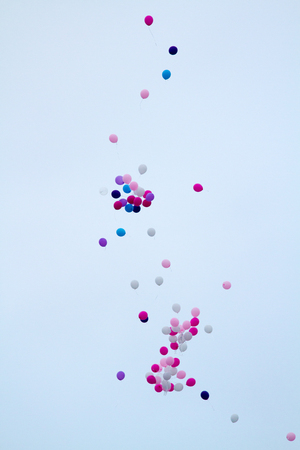 Balloons over a clear white sky.