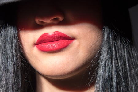 Portrait of beautiful young woman with red lips on black background Stock Photo