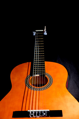 A classical guitar with isolated black background