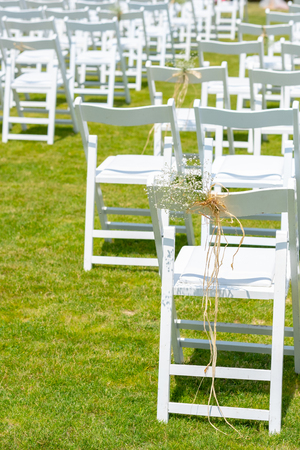 White chairs decorated with flowers, are in the zone of the wedding ceremony
