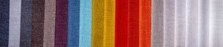 Rainbow clothes background. Pile of bright folded clothes