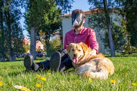Boy wearing old style virus mask   with his dog playing at garden Stockfoto