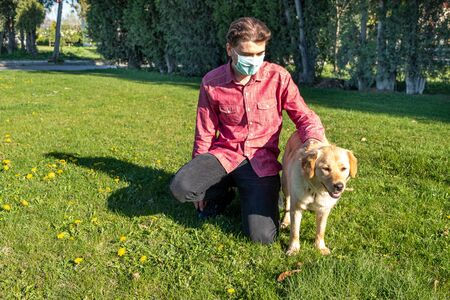 Boy wearing virus mask with his dog playing at garden