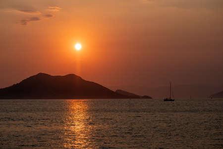 Boat at sea while sun sets