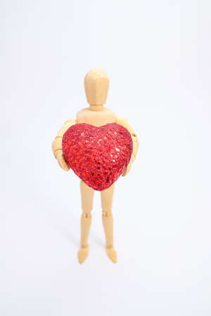 wooden human holding red heart shape mean love Stock Photo