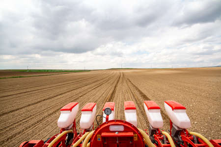tractor sowing of seed to field at spring time Stock Photo