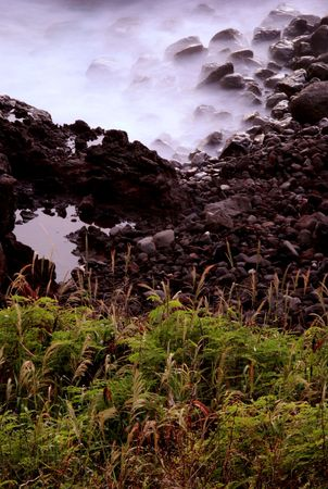 Rocks in waves, green forground