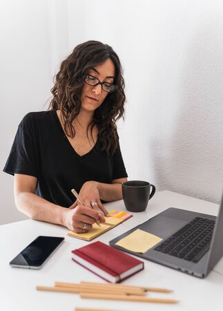 Vertical photo of a woman with glasses writing on a notes sitting in front of a table with a laptop, a notebook, a mobile, pencils and a cup of coffee