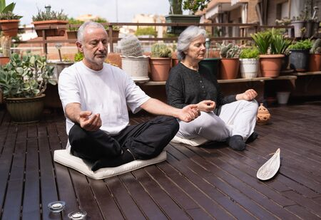 A senior man and woman with white hair meditating on a wooden terrace surrounded by plant candles and incense
